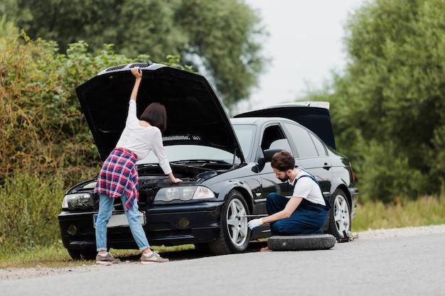 Mujer comprobando motor y hombre intercambiando neumáticos