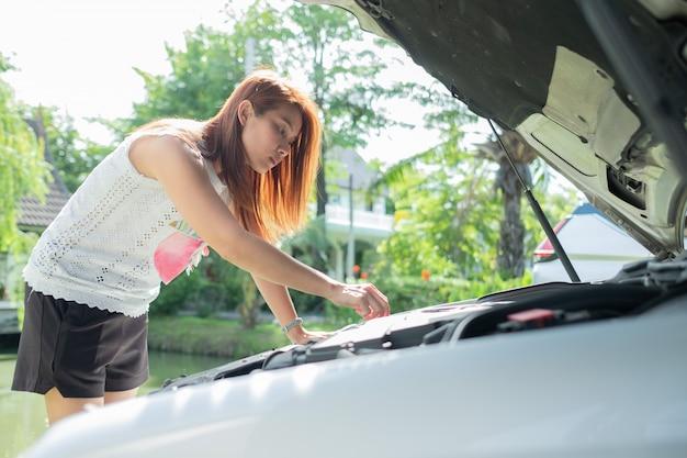 Mujer comprobando el nivel de aceite en un automóvil, cambie el automóvil de aceite