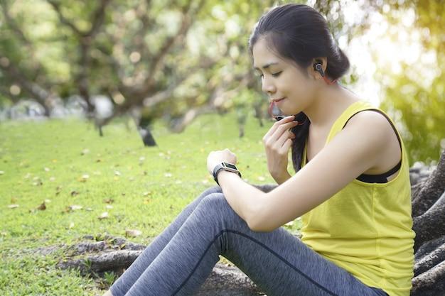 Mujer comprobando el progreso en el reloj inteligente conectar escuchar música al auricular