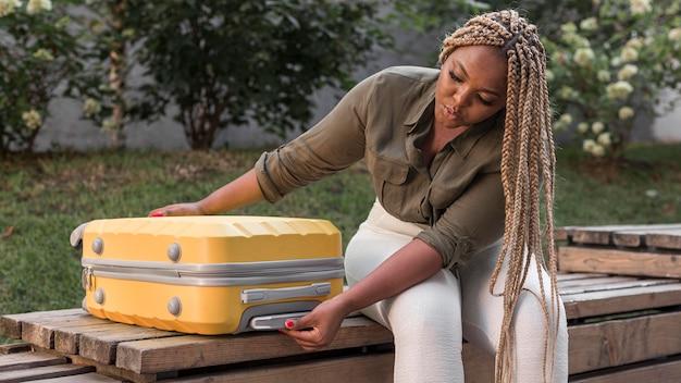 Mujer comprobando su equipaje amarillo