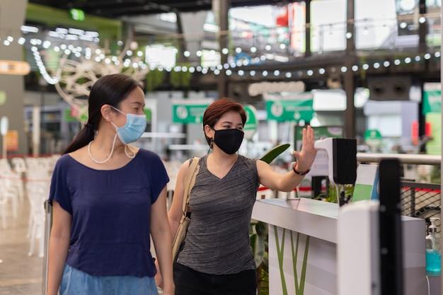 Mujer comprobando la temperatura corporal por termómetro digital infrarrojo con su mano