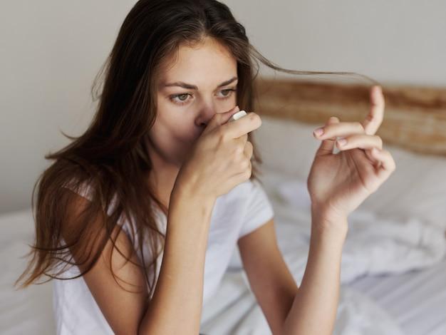La mujer comprueba la temperatura con un termómetro en la boca.