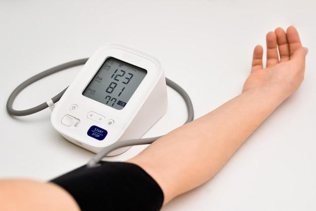 Mujer compruebe el monitor de presión arterial y el monitor de frecuencia cardíaca con manómetro digital