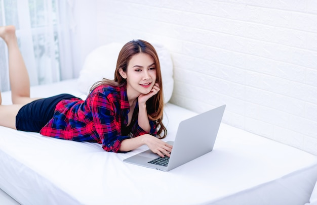 La mujer y la computadora en la sala blanca trabajo feliz el concepto de trabajo feliz en casa