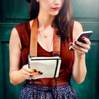 La mujer comunica el teléfono fuera del concepto de la ciudad