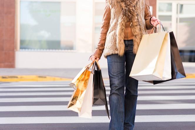 Mujer con bolsas de compras en el paso de peatones
