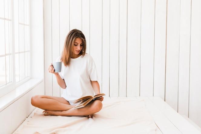Mujer con el libro de lectura de la taza en la superficie blanca