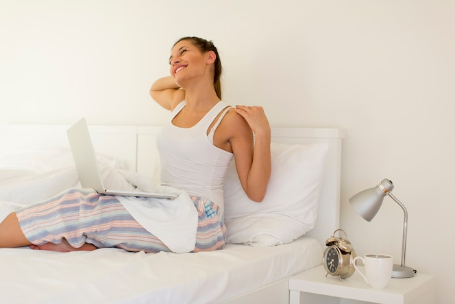 Mujer con laptop en la cama