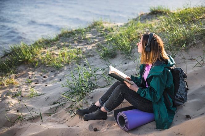 Mujer con libro disfrutando de la música