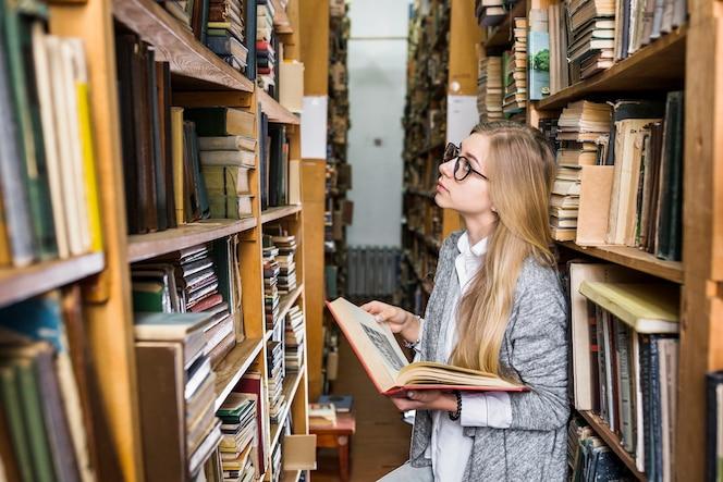 Mujer con libro mirando hacia arriba