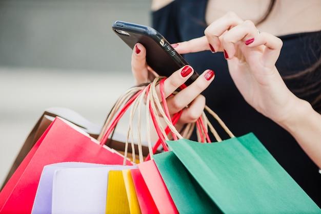 Mujer con los bolsos de compras que sostienen el smartphone