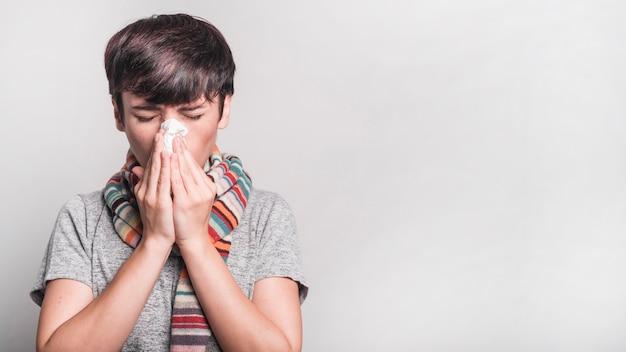 Mujer con los ojos cerrados que sopla su nariz en el papel de seda contra el fondo gris