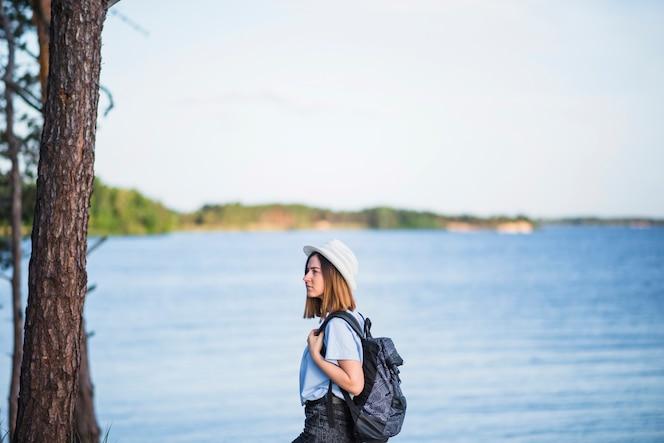 Mujer con mochila cerca del lago