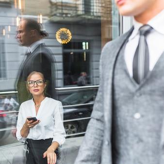 Mujer con smartphone mirando empresario
