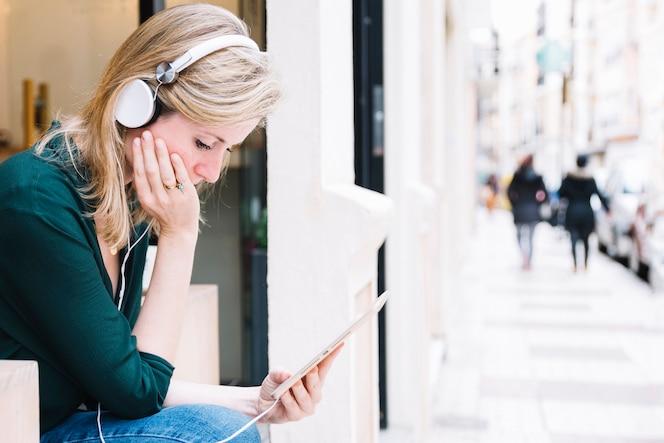 Mujer con tableta sentado en la calle