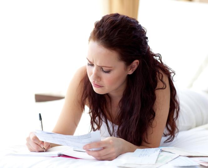 Mujer concentrada escribiendo notas en la cama