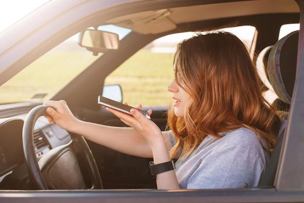Una mujer concentrada gira la rueda en el automóvil, hace una llamada de voz a través del teléfono celular, habla con amigos mientras conduce un automóvil