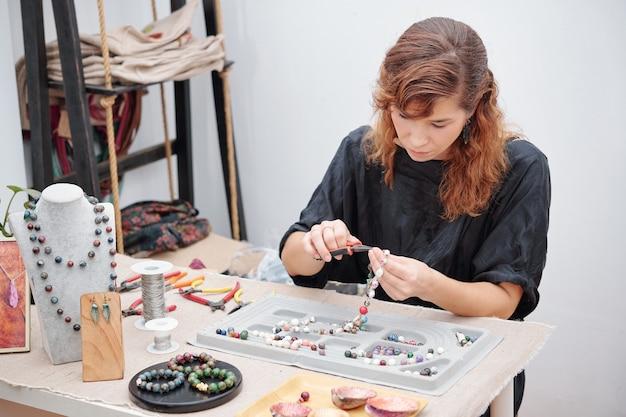 Mujer concentrada en hacer joyas