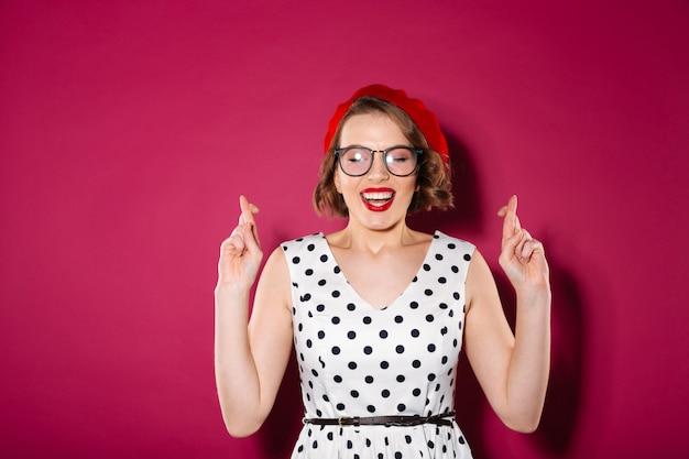 Mujer concentrada de jengibre con vestido y anteojos rezando con los dedos cruzados y los ojos cerrados sobre rosa