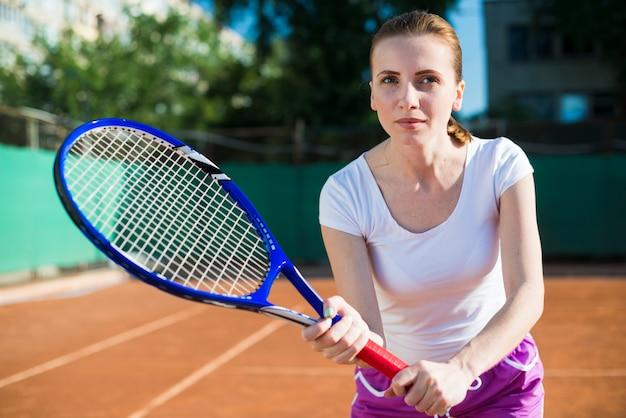 Mujer concentrada jugando al tenis