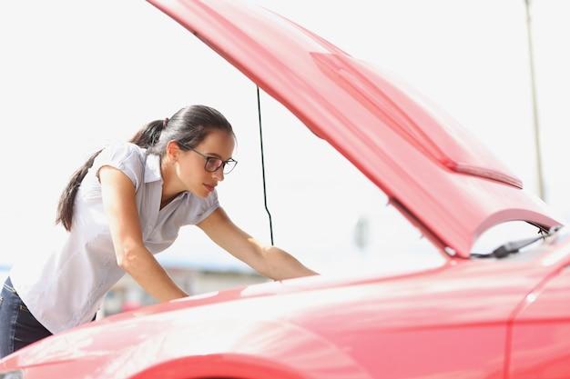 Mujer concentrada mira avería del coche del motor del coche en el concepto de la carretera