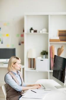 Mujer concentrada que codifica la información en la computadora