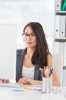 Mujer concentrada usando la computadora en la oficina