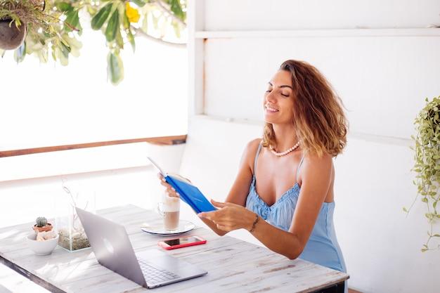 Mujer de concepto de trabajo a distancia en café de verano con portátil