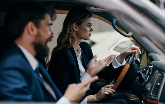 Una mujer conduciendo un automóvil junto a un hombre colegas en el viaje de trabajo funcionarios.