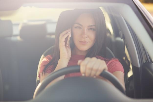 Mujer conduciendo un automóvil, tiene una conversación telefónica, se atasca en un embotellamiento, mira a través de winowshileld