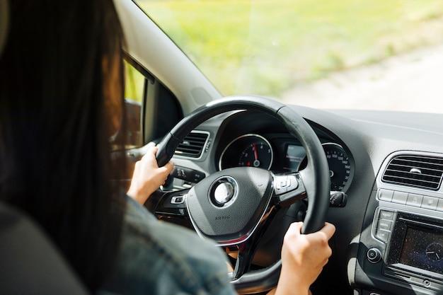 Mujer conduciendo un coche en un entorno rural