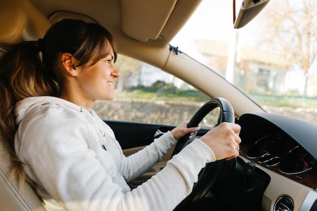 La mujer conduciendo el coche moderno.
