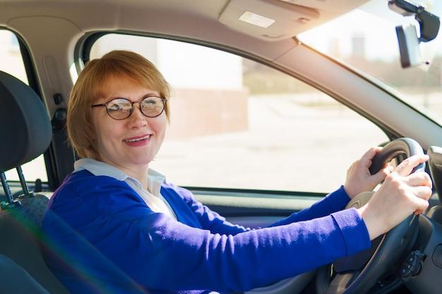 Una mujer conduciendo un coche. una mujer de mediana edad con gafas sonríe.
