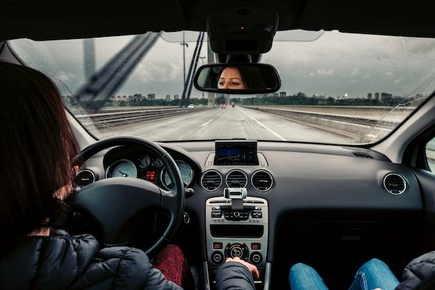 Mujer conduciendo el coche sobre el puente