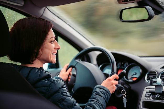 Mujer conduciendo coche y sonriendo