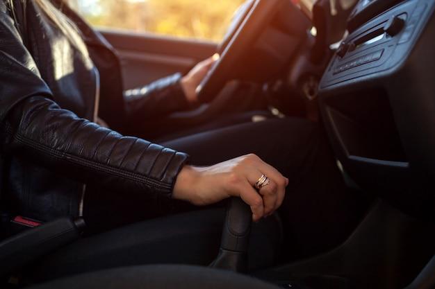 Mujer conduciendo. conductor de la mano en la transmisión y el volante. propietario arrancando su auto