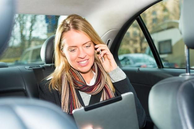 Mujer conduciendo en taxi, ella está hablando por teléfono