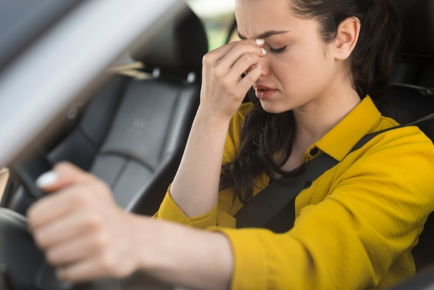 Mujer conduciendo y teniendo dolor de cabeza