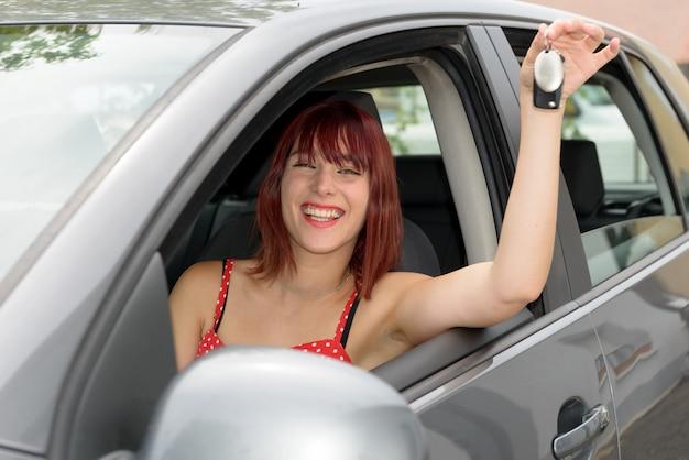 Mujer del conductor del coche sonriendo mostrando nuevas llaves y coche