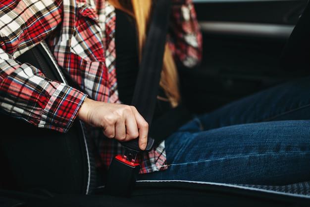 Mujer conductora se abrocha el cinturón de seguridad en el coche