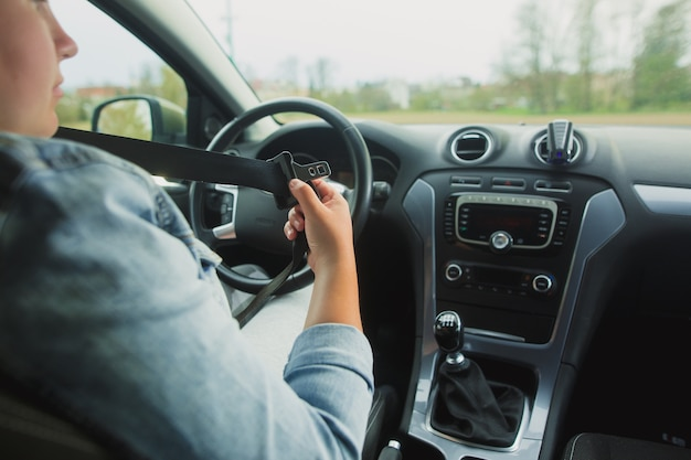 Mujer conductora abrocharse el cinturón de seguridad antes de conducir, concepto de conducción segura