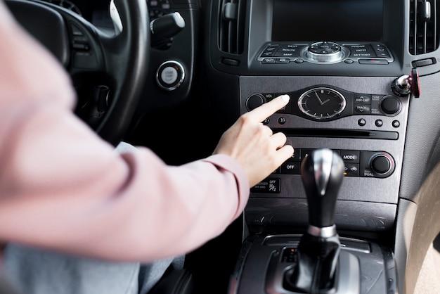 Mujer conductora ajustando la configuración de su automóvil