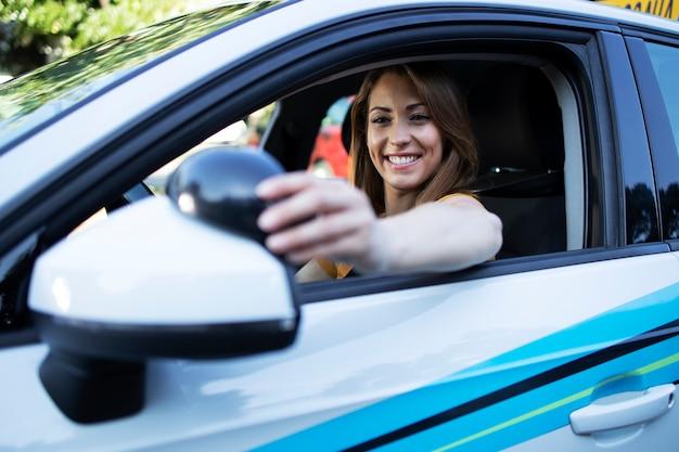 Mujer conductora ajustando los espejos antes de conducir un coche