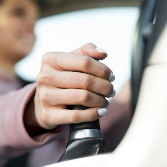Mujer conductora borrosa cambiando los engranajes