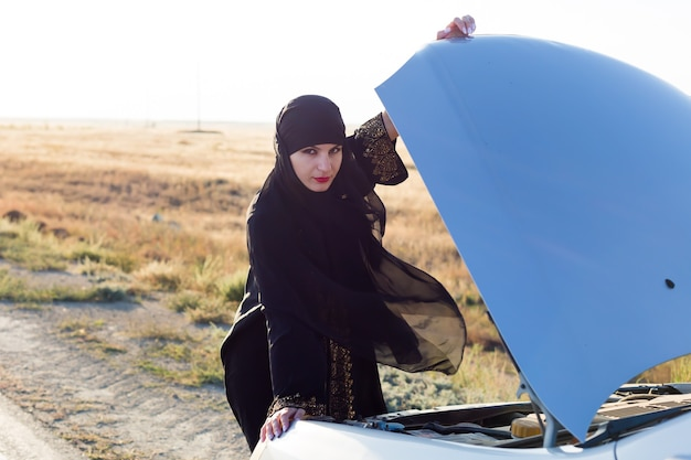 Mujer conductora mirando el motor del coche roto mientras sostiene el capó con la mano