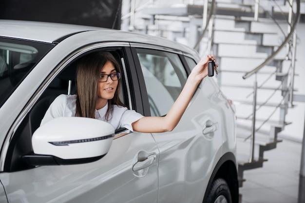 La mujer conductora sonriendo mostrando nuevas llaves del auto