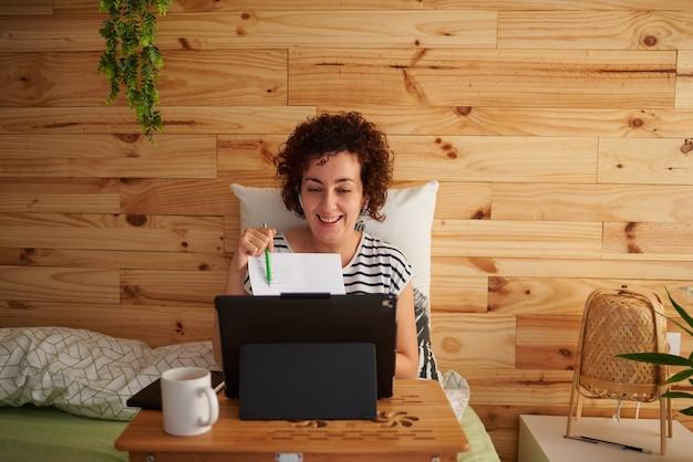 Mujer en una conferencia de teletrabajo desde su cama apuntando a un papel
