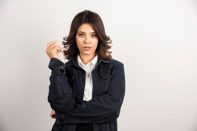 Mujer confiada en chaqueta de mezclilla de pie en blanco.