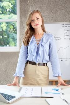 Mujer confiada joven que se coloca en el escritorio de oficina y que mira la cámara