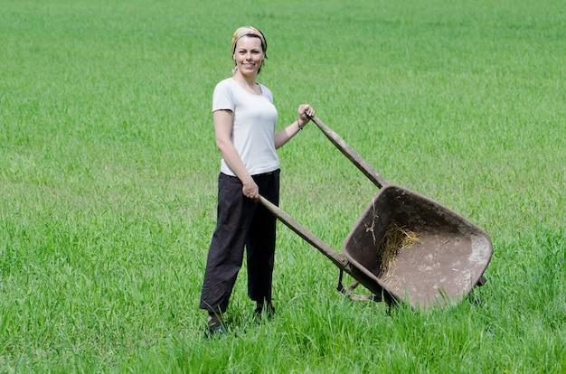 Mujer confiada que trabaja con una carretilla de mano en una granja